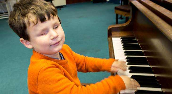 A small blind boy plays the piano