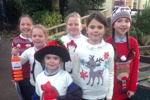 A group of children collecting funds in Christmas jumpers